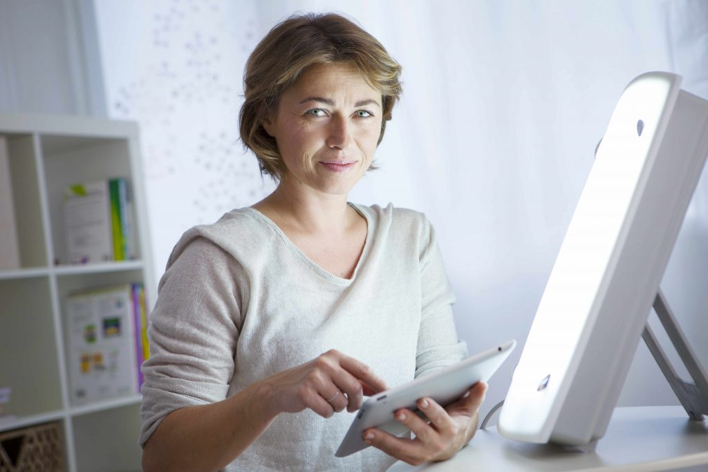 woman sitting with a light therapy lamp for SAD or depression