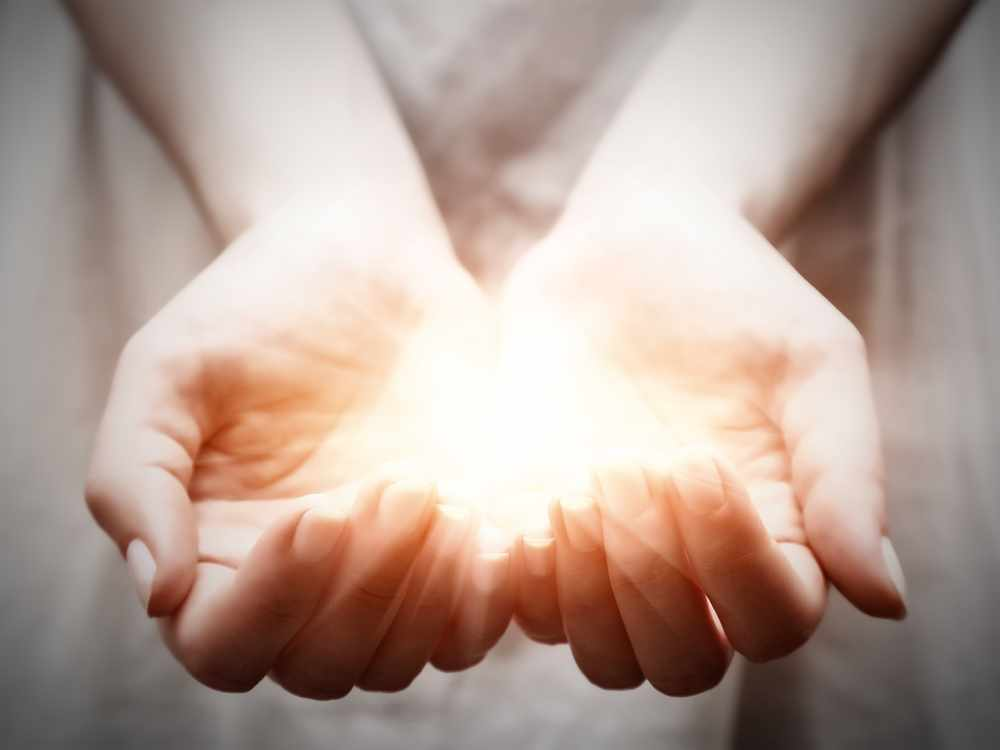 a woman holding a bright shining light in the palm of her hands