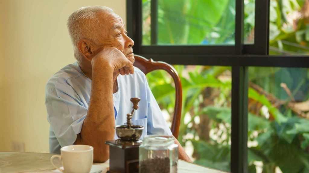 Un anciano está sentado a la mesa y mira por la ventana en silencio
