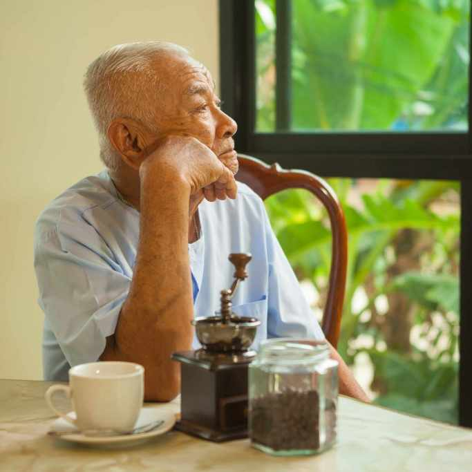 an older man sitting at a table, quietly staring out the window