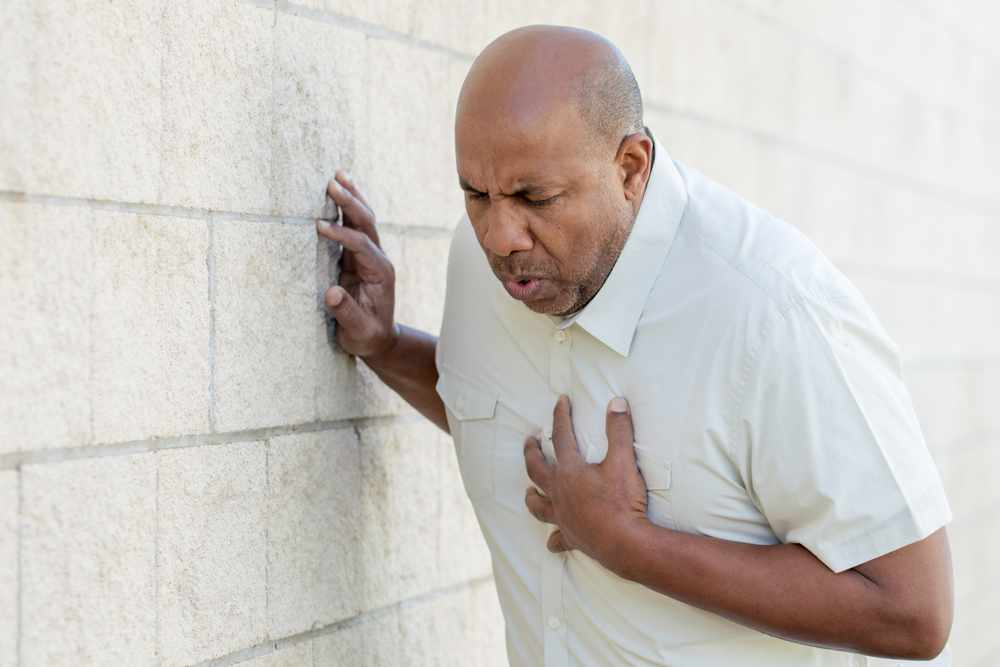 a middle-aged African American man holding his chest and leaning against a wall, maybe a heart attack or stroke