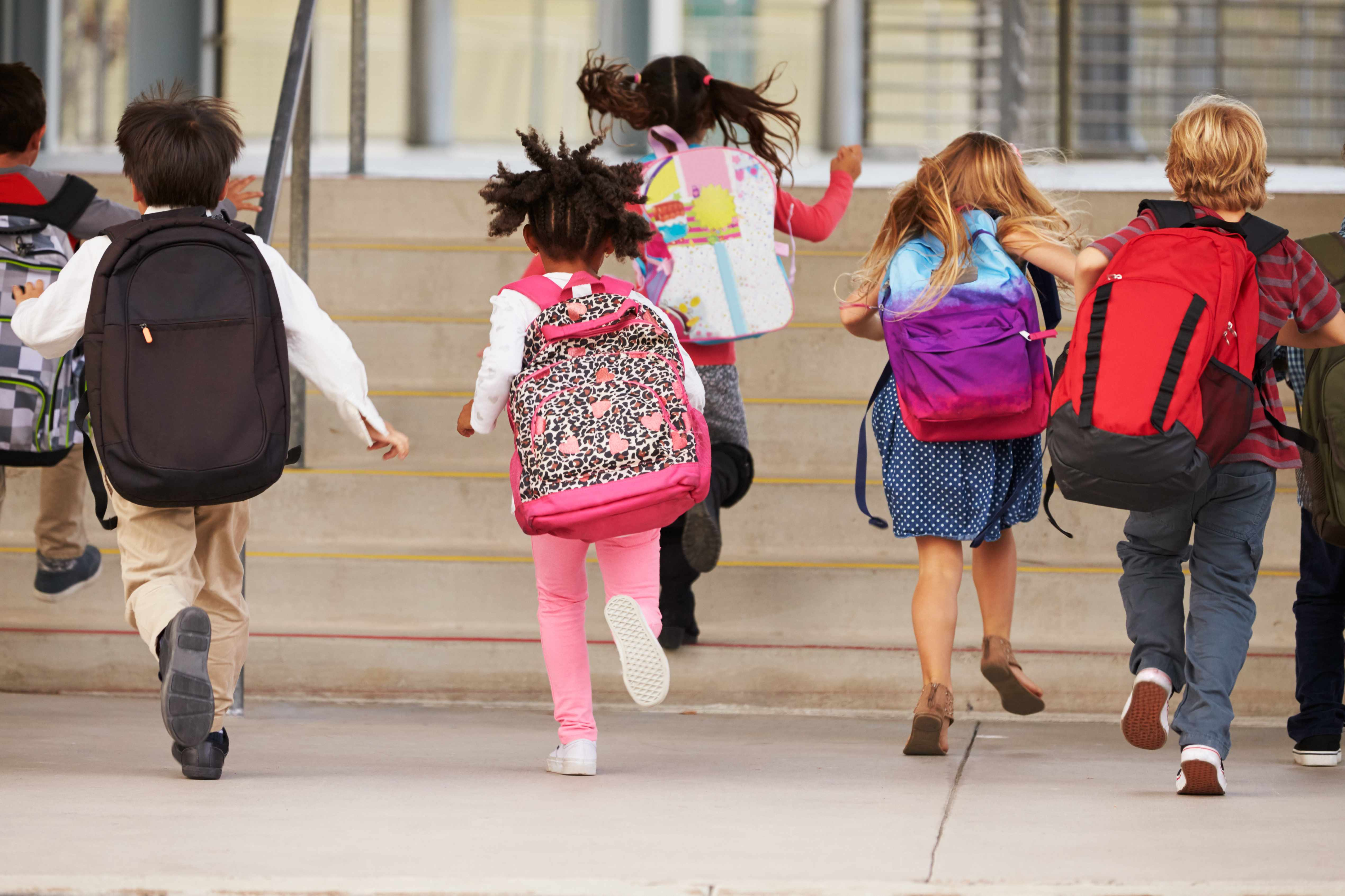 a group of elementary students running up the stairs wearing backpacks