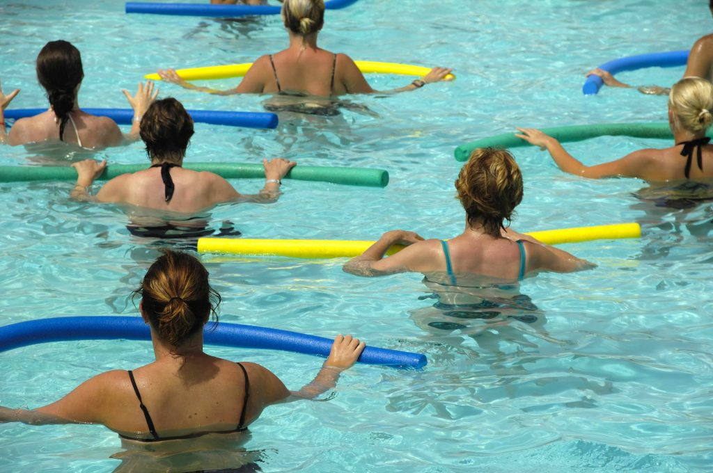 a group of women in a swimming pool exercising and doing water aerobics