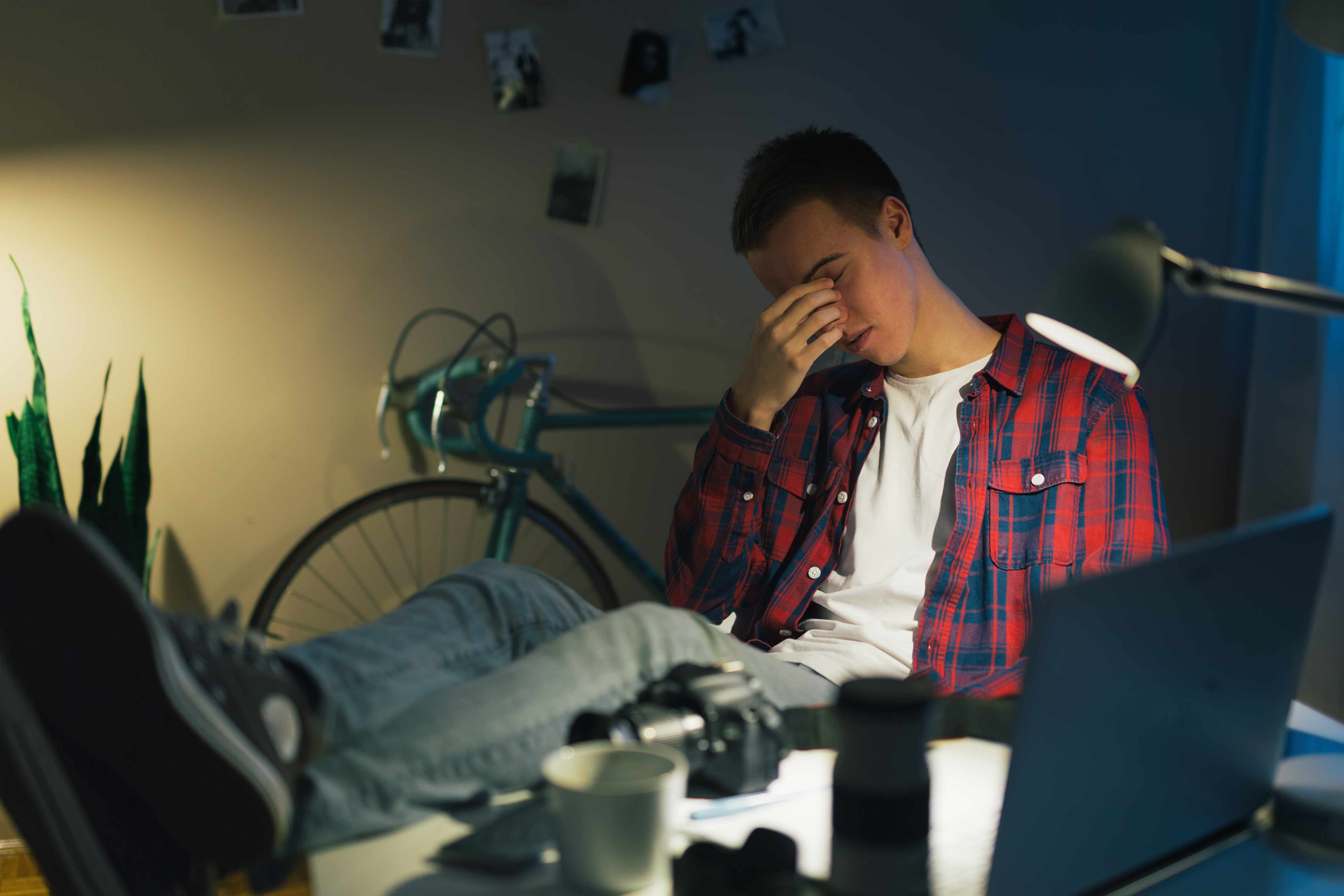 a young teen or college boy sitting at his computer rubbing his eyes tired and exhausted