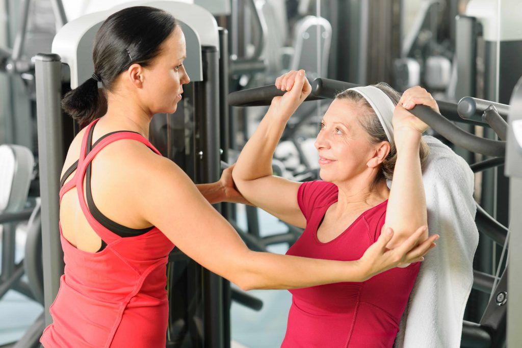 a middle-aged woman working out in a gym with help from a coach