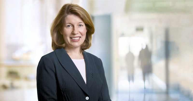 Dr. Deborah Rhodes in a blue suit standing in a hospital hallway