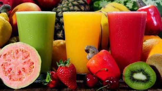 Varias frutas enteras y tres vasos de batidos de fruta