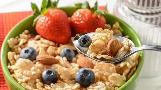 High fiber bowl of cereal with berries and almond nuts.