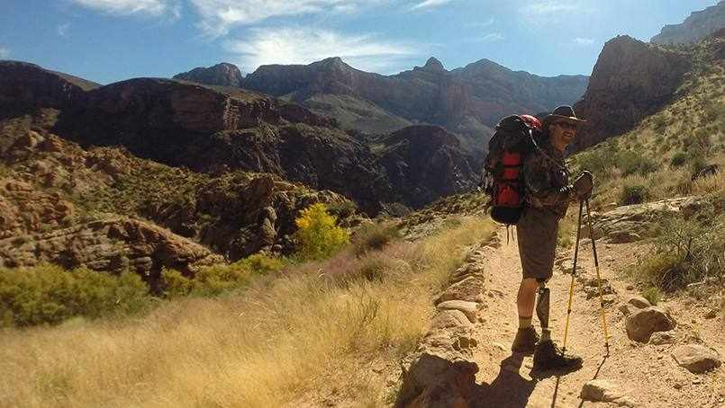 patient Randy Herlein walking on trail with his prosthetic leg