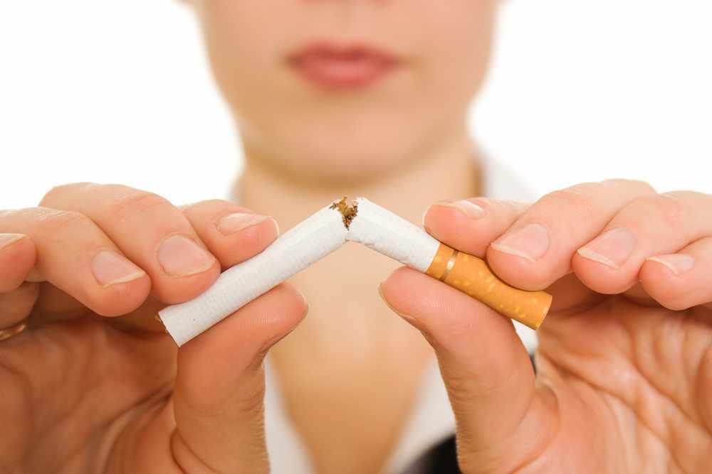 A woman breaks a cigarette smoking
