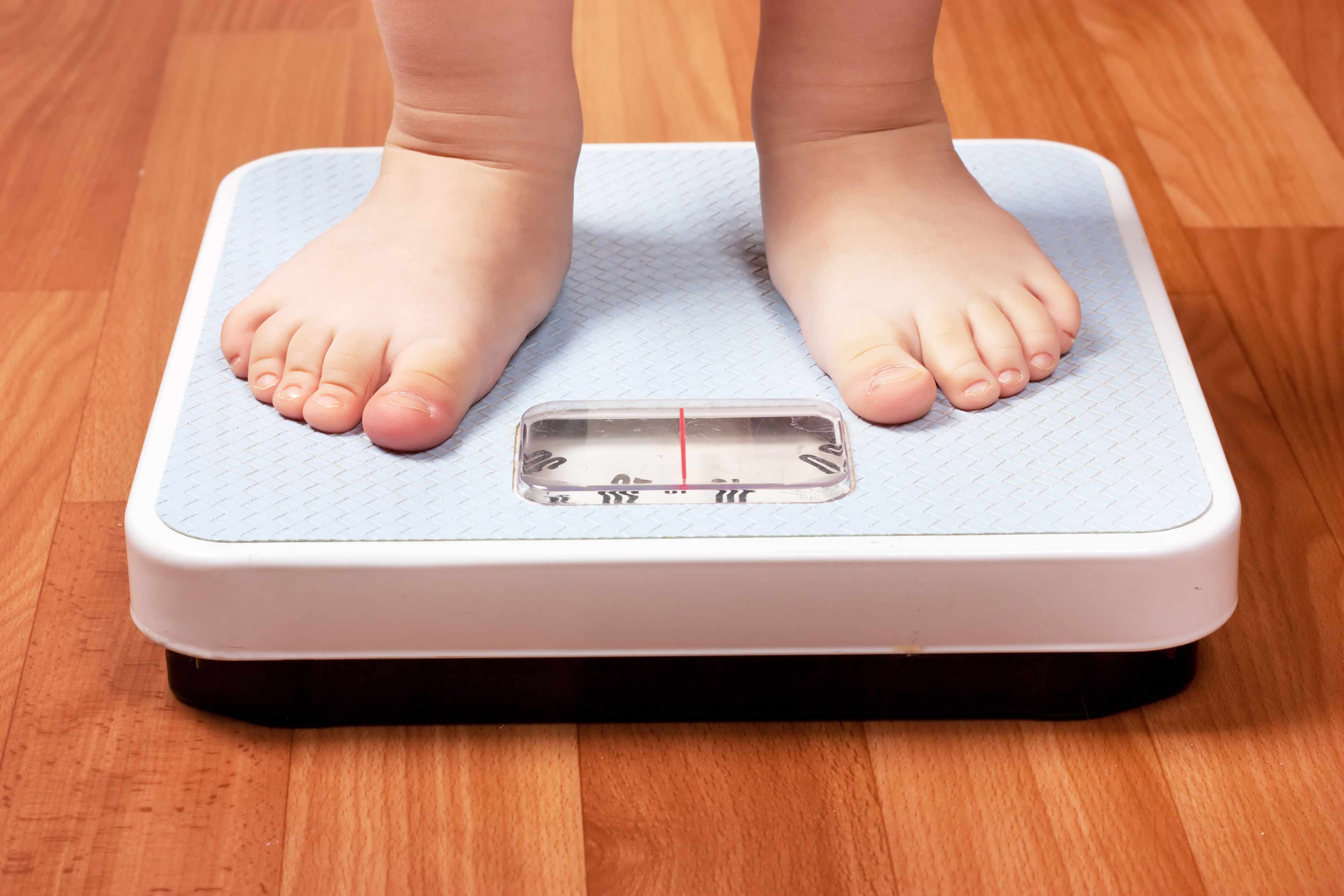 child's feet on a scale obesity