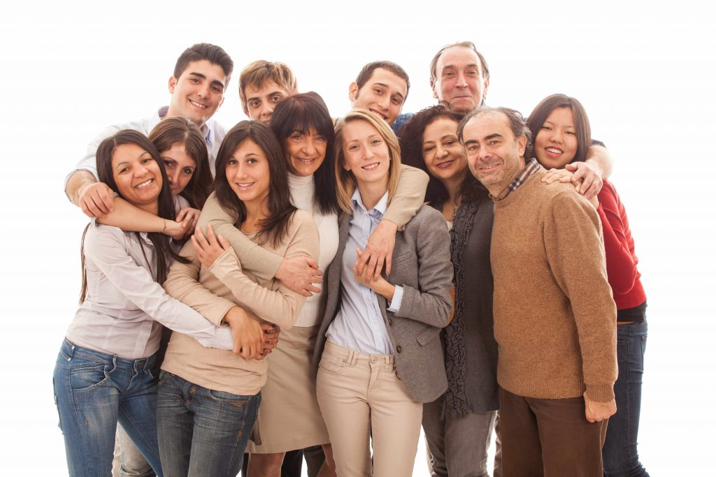 a multigenerational, multi-ethnic group of people standing together, smiling and hugging