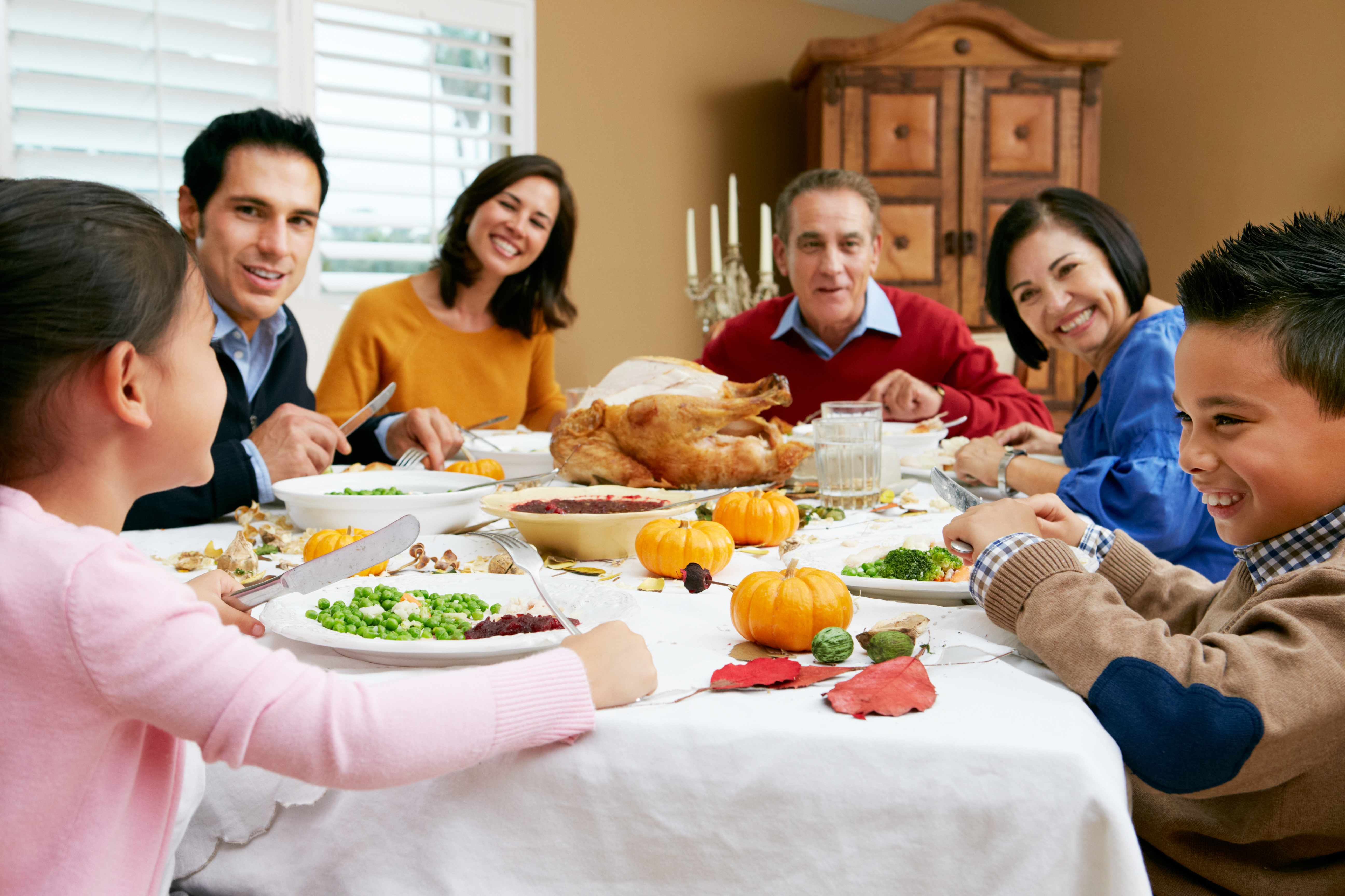 a family around a holiday dinner table laughing and talking
