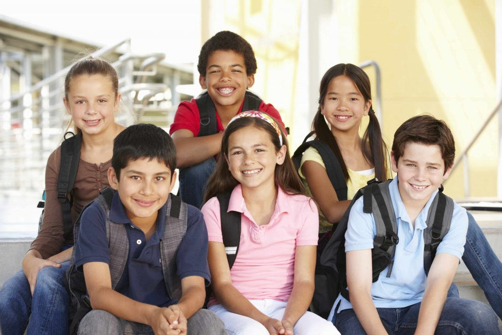a group of smiling young adolescent boys and girls