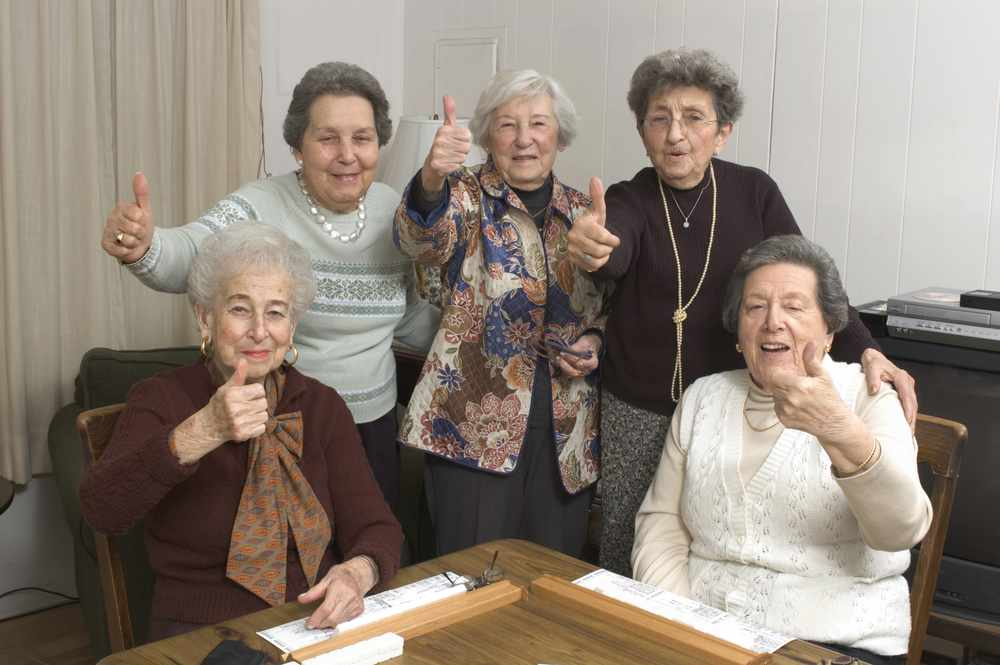 a group of happy senior women friends playing mahjong