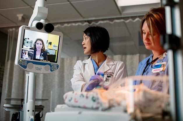 Neonatologist looking at telemedicine machine
