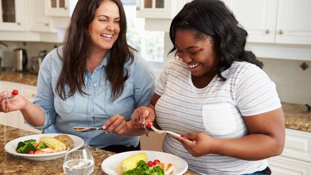 two women in the kitchen preparing a healthy meal