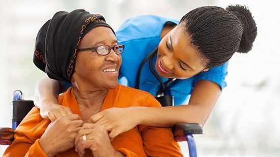Una mujer cuida de una anciana afroamericana sentada en una silla de ruedas