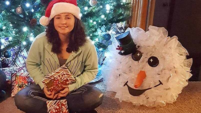 cancer patient Beth Lepper holding presents and sitting beside Christmas tree