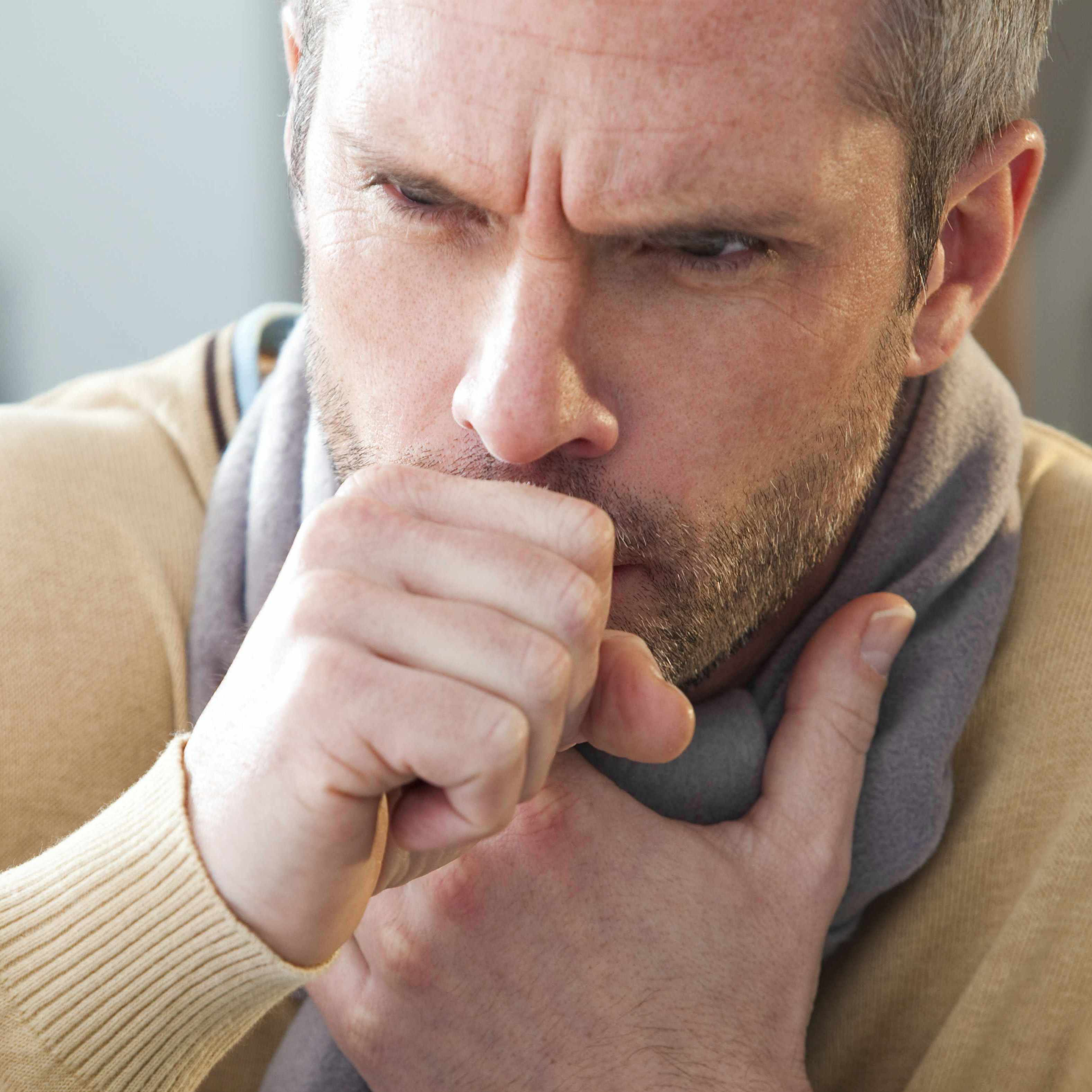 a Caucasian man with a scarf and coughing