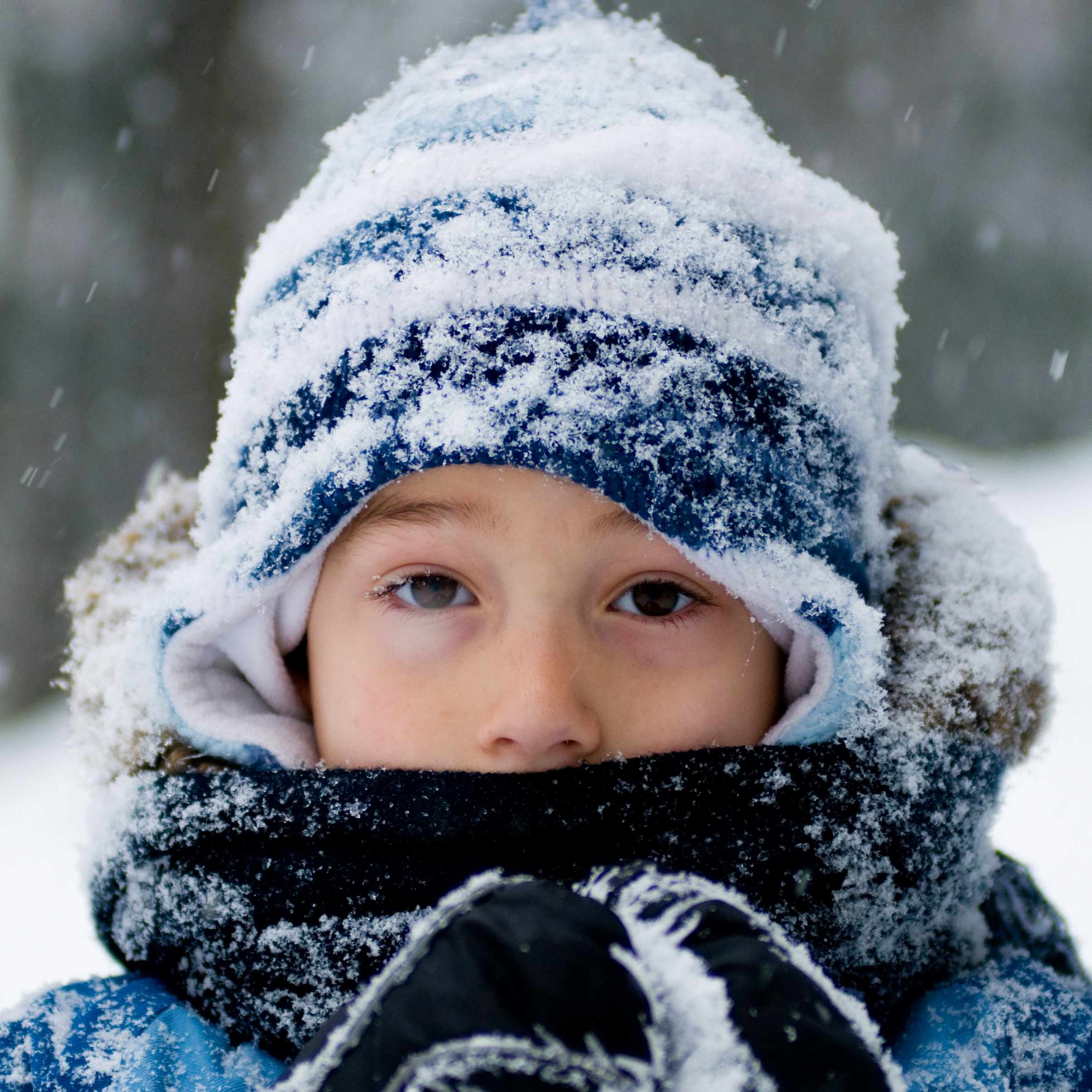a cold little boy bundled up in winter clothes with snow falling