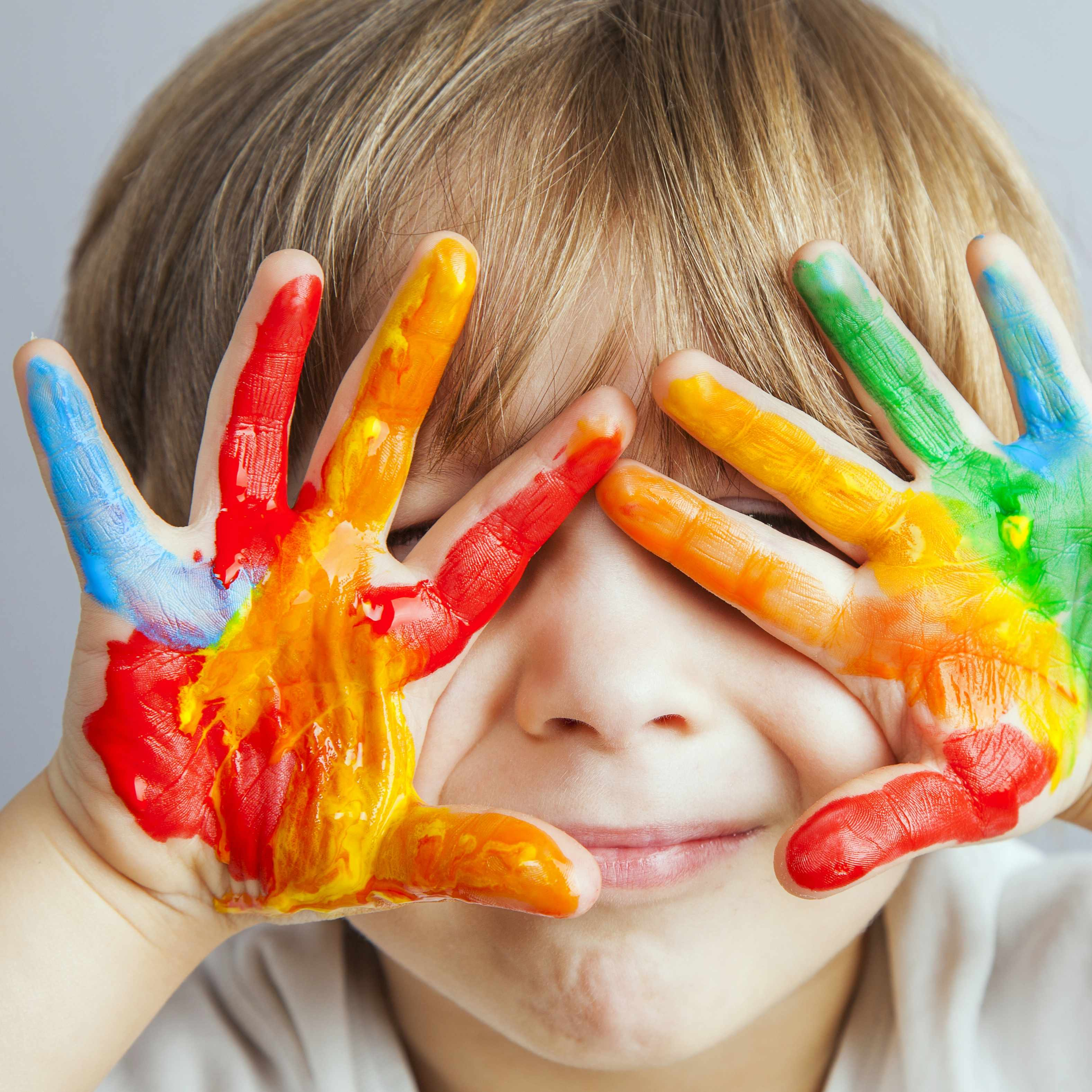 a little boy holding his messy paint covered hands over his face