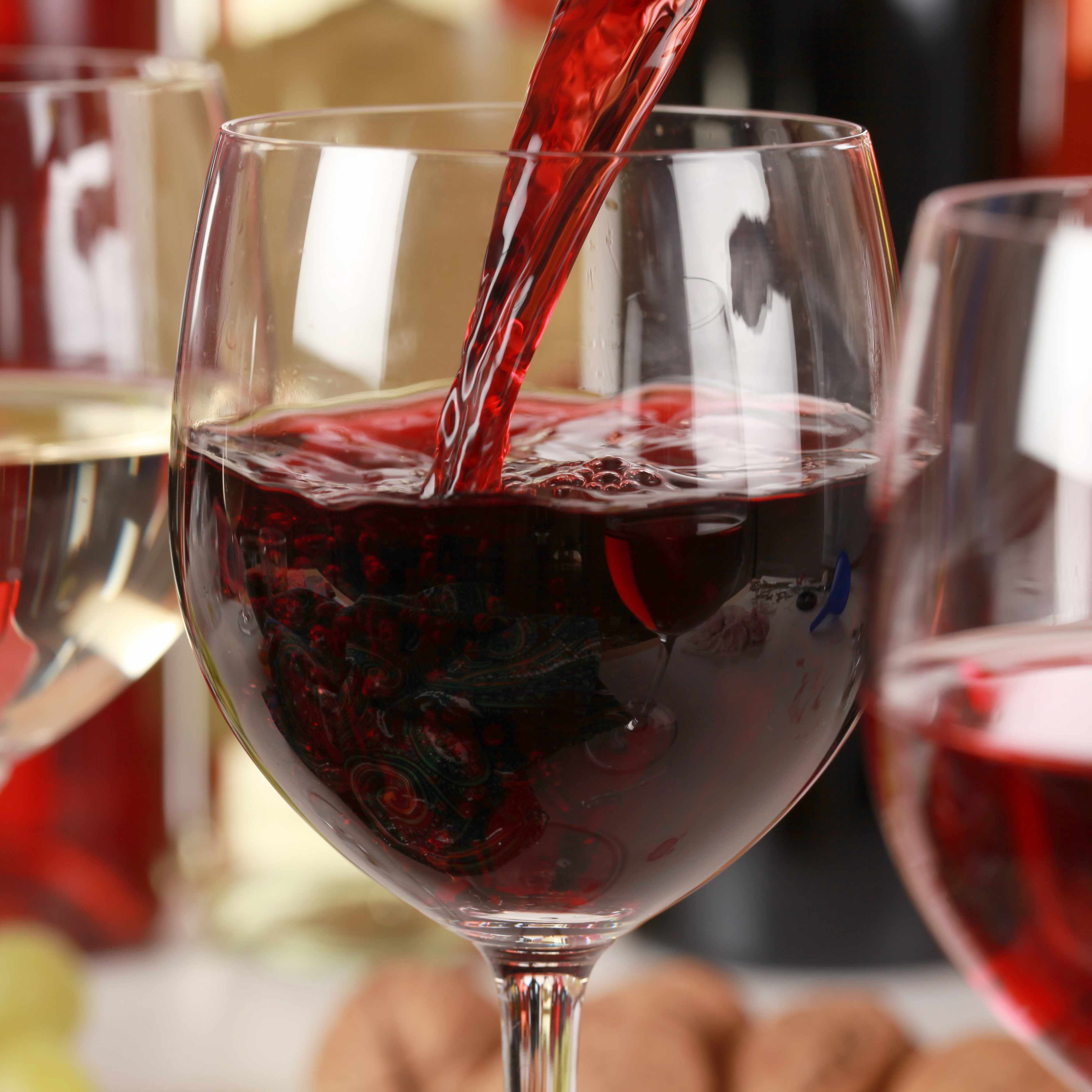 a row of three wine glasses containing white and red wines