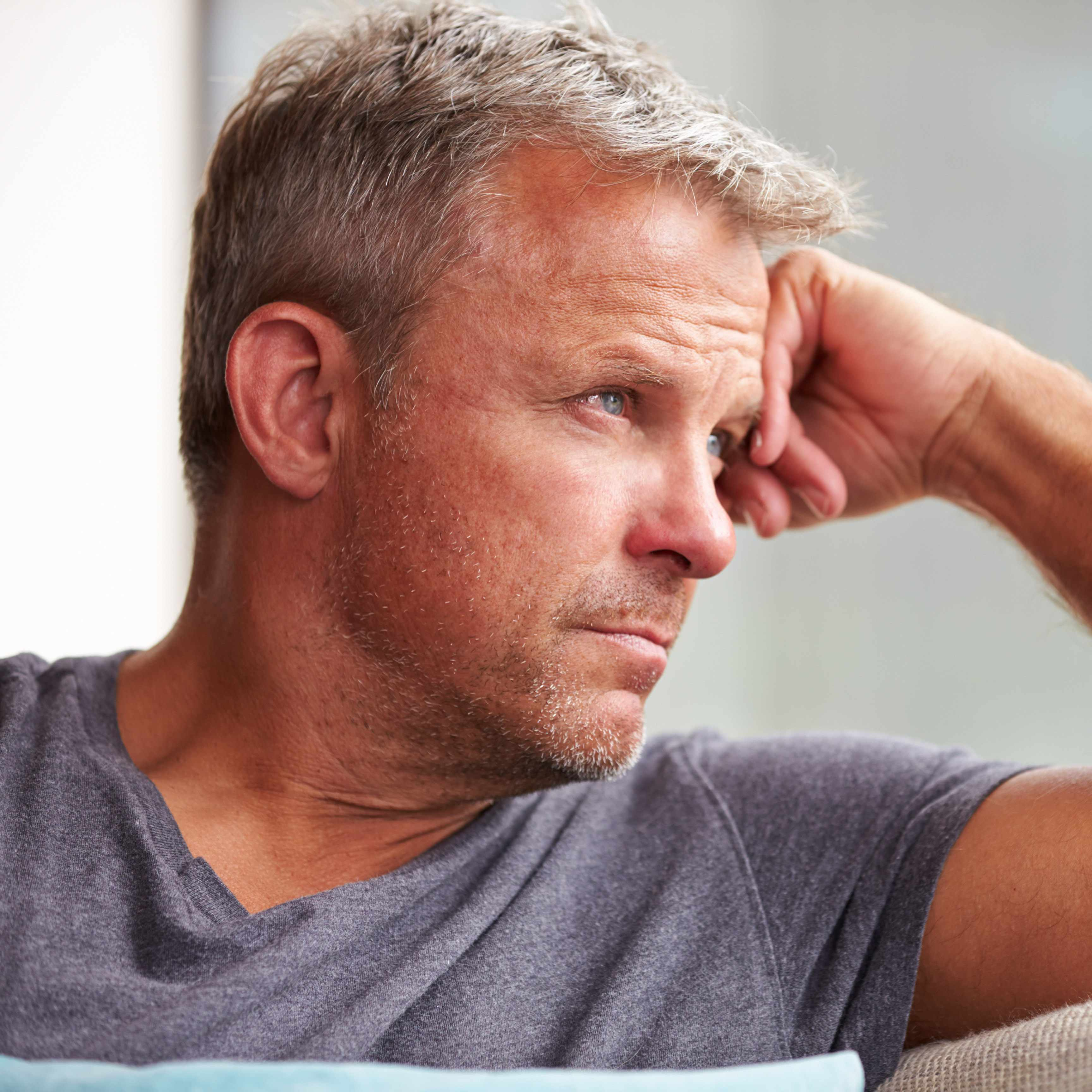 a serious-looking middle-aged man in profile, with his forehead resting on his hand, staring off into the distance