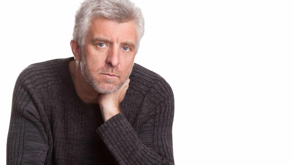 Un hombre de mediana edad y apariencia seria mira fijamente a la cámara, mientras se sostiene el mentón con la mano