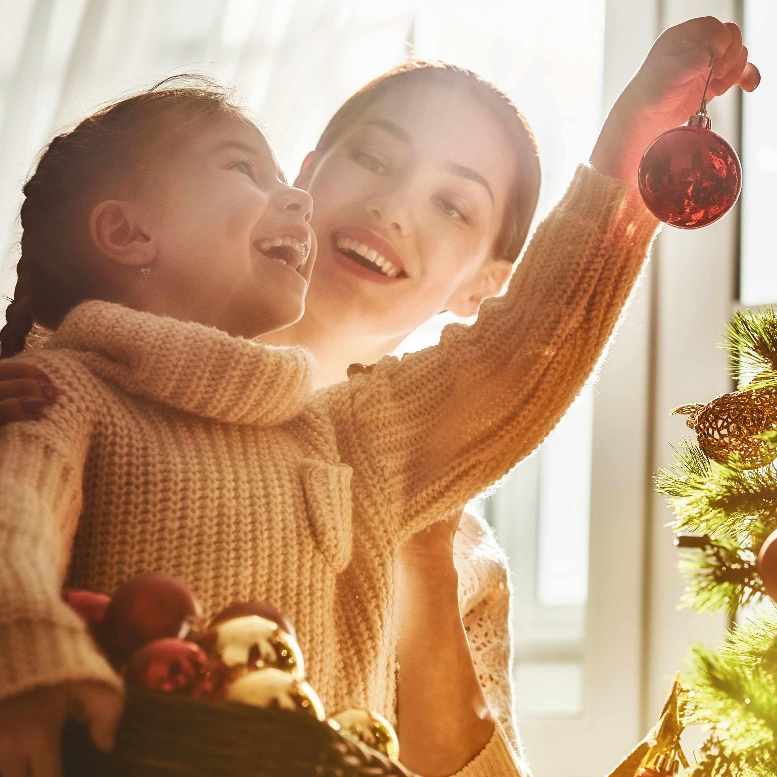 a woman holding a little girl near the Christmas tree and putting up ornaments