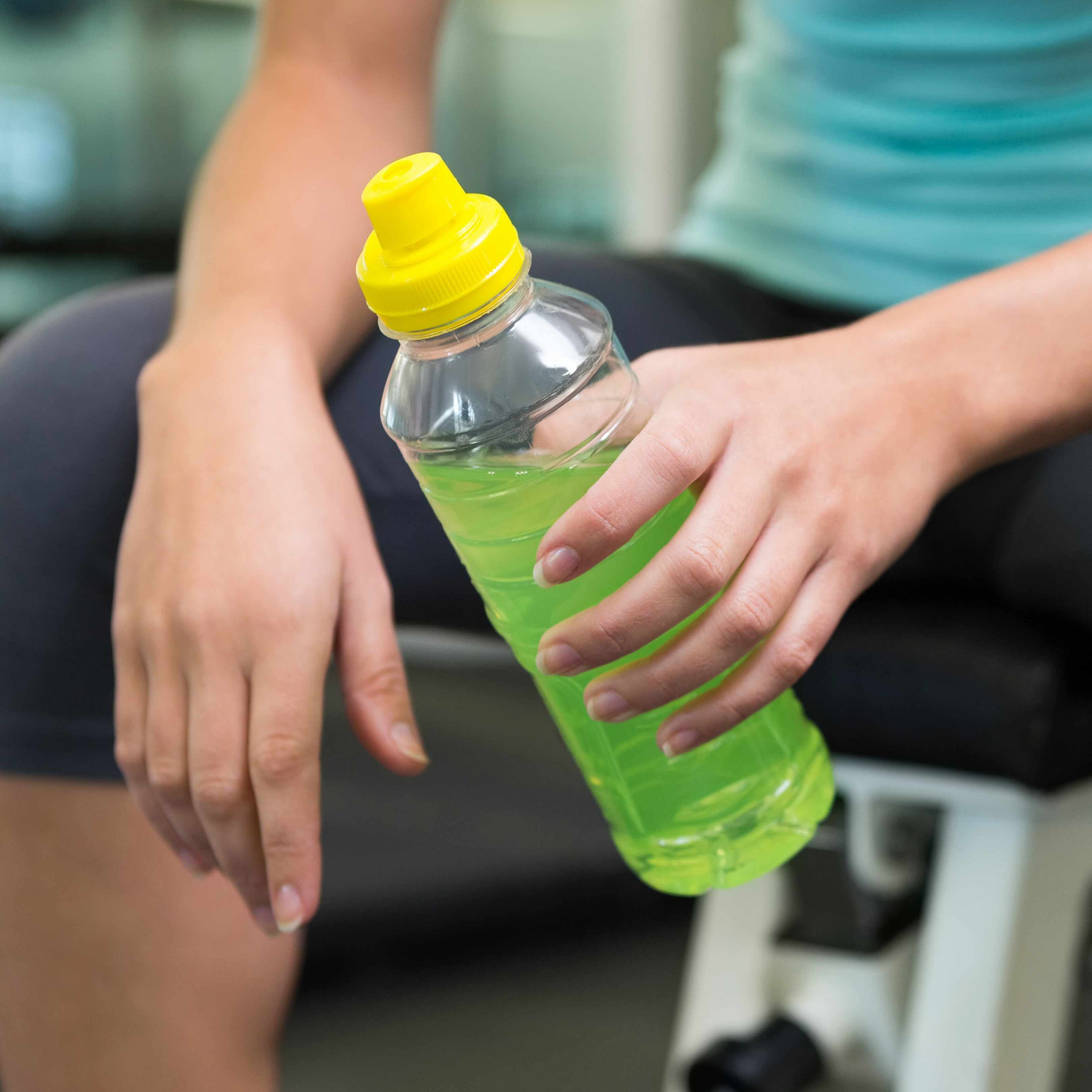 a woman sitting and resting after exercising, holding an energy sports drink