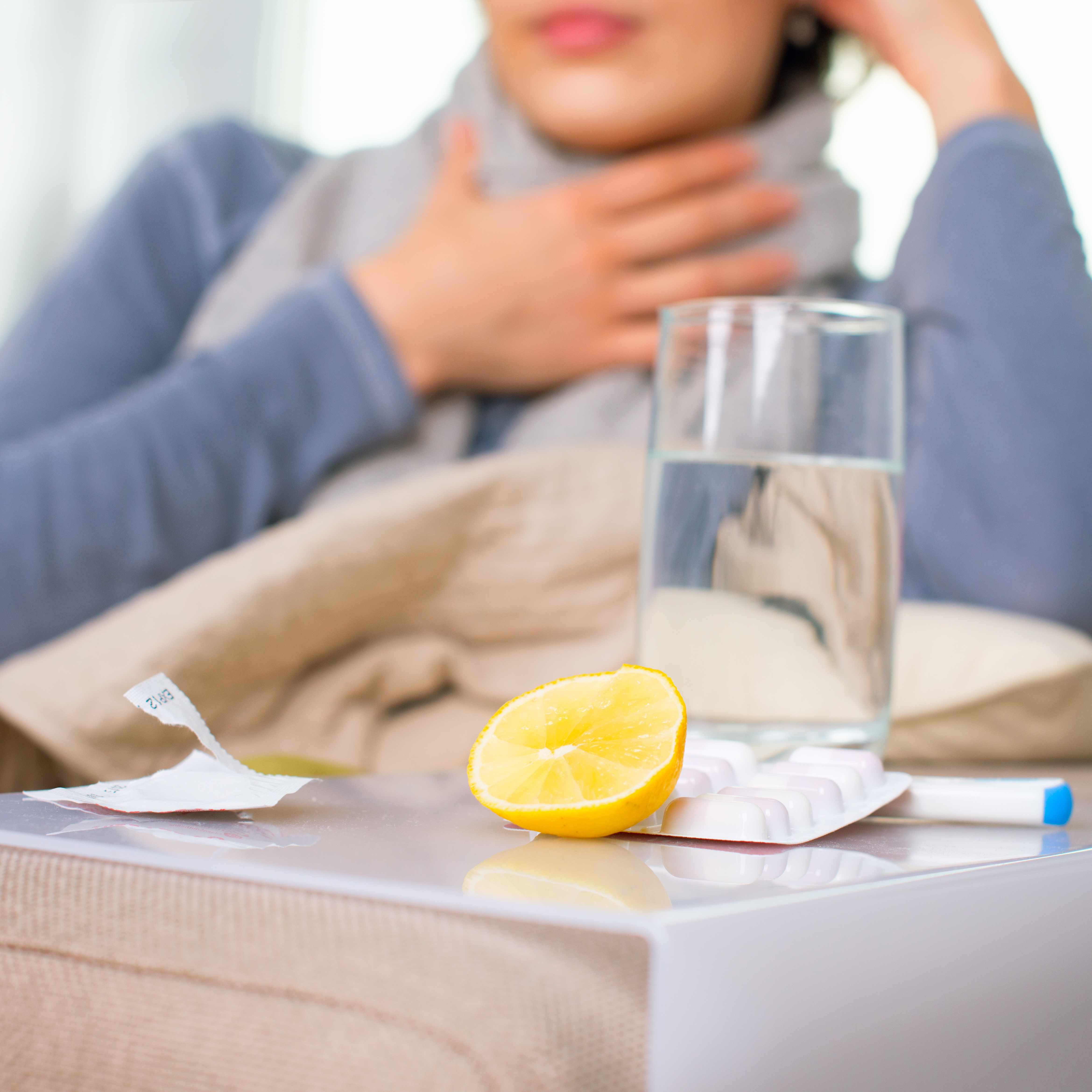 a woman sitting on a couch, with a scarf around her neck and her hand to her throat, with a glass of water, a lemon, and some medication on a table in the foreground