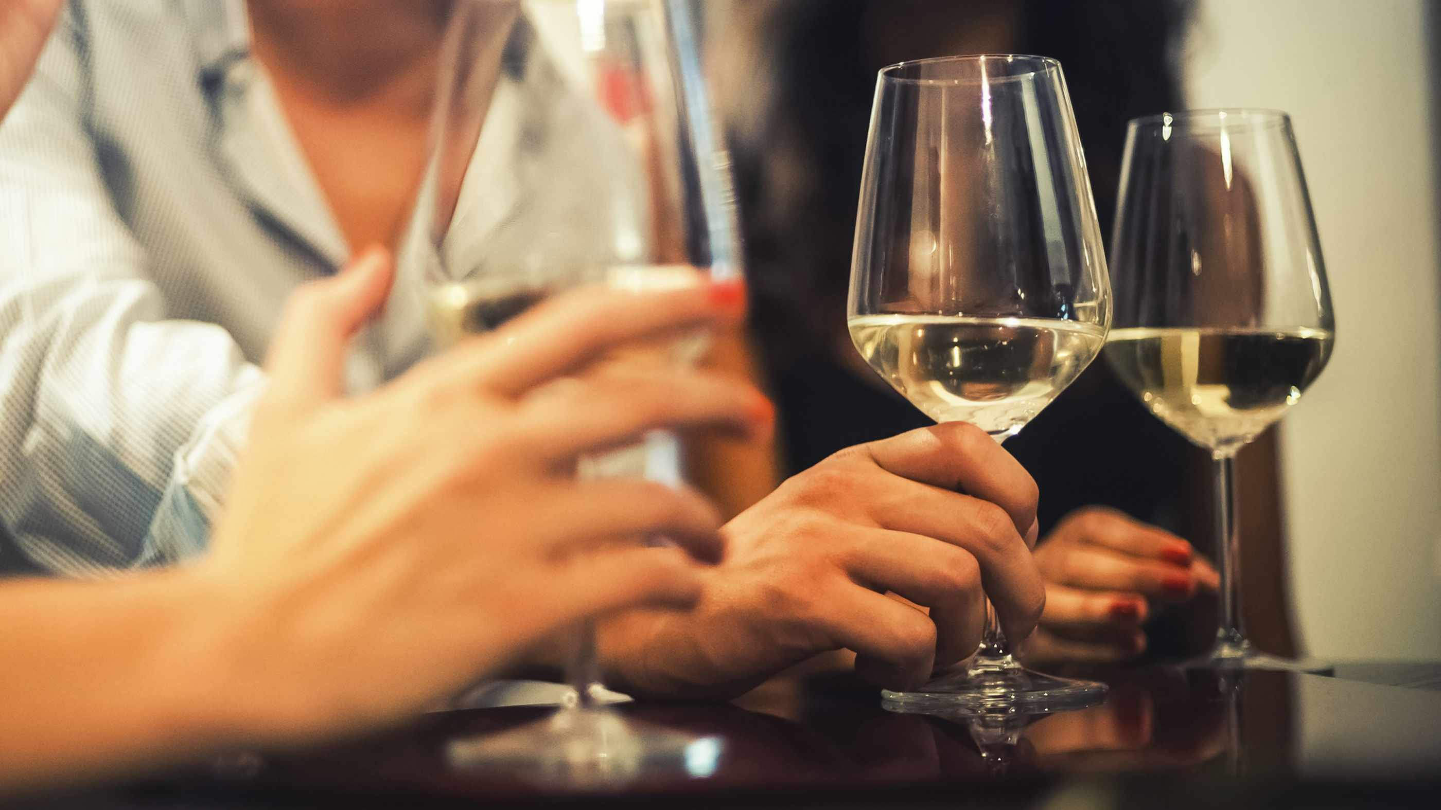 several people at a table or bar holding glasses of wine to drink