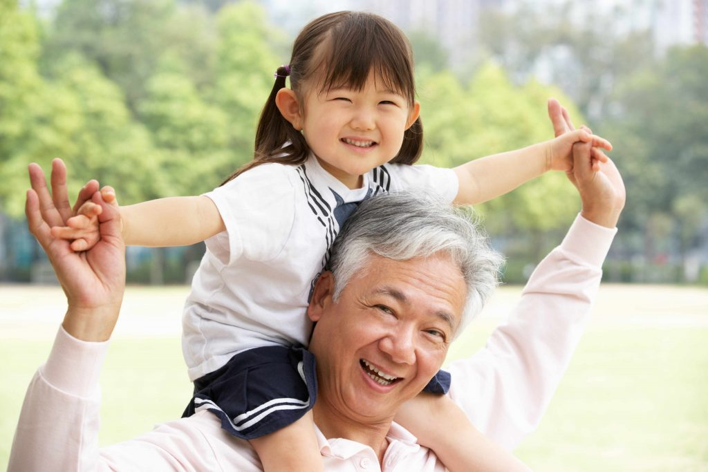 a close-up of a smiling grandfather and granddaughter, outdoors on a sunny day, with her riding on his shoulders