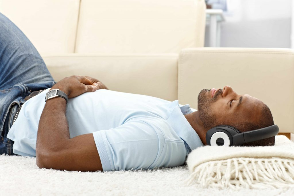 a young man lying on the floor, with his head resting on a folded blanket, peacefully listening to music with headphones