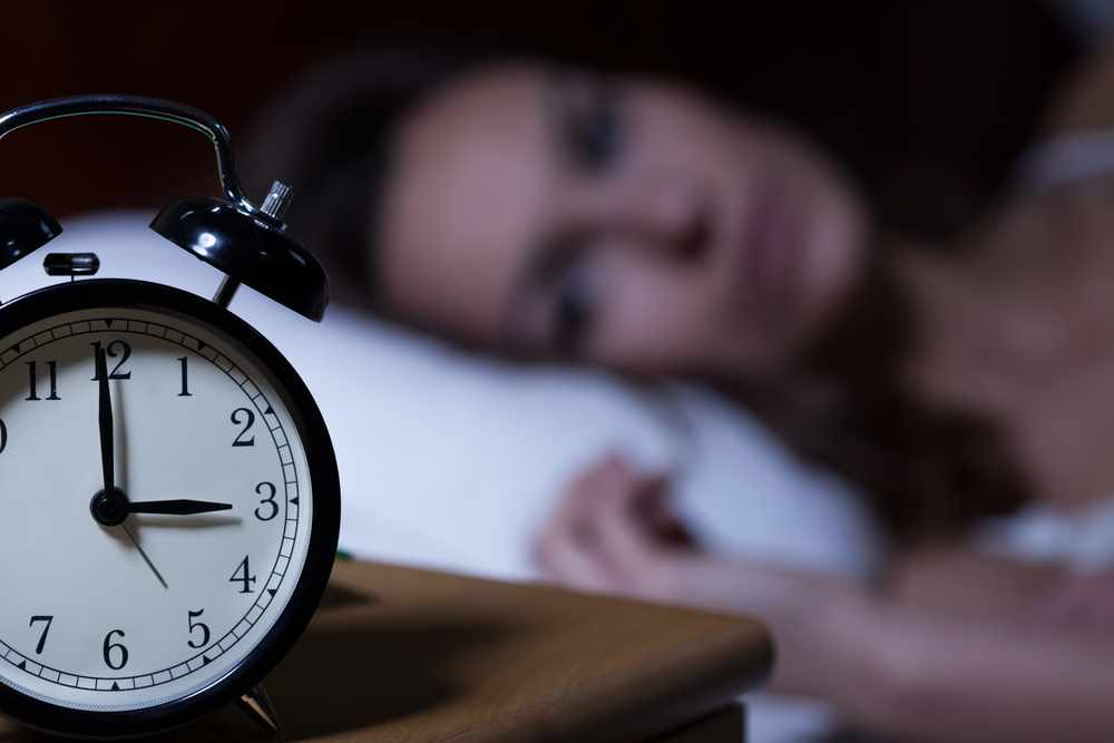 a close-up of an alarm clock reading 3 o'clock, with a wide awake woman lying on a pillow in the background, out of focus