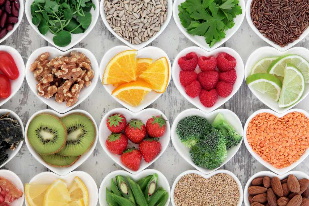 heart-shaped bowls of various healthy foods