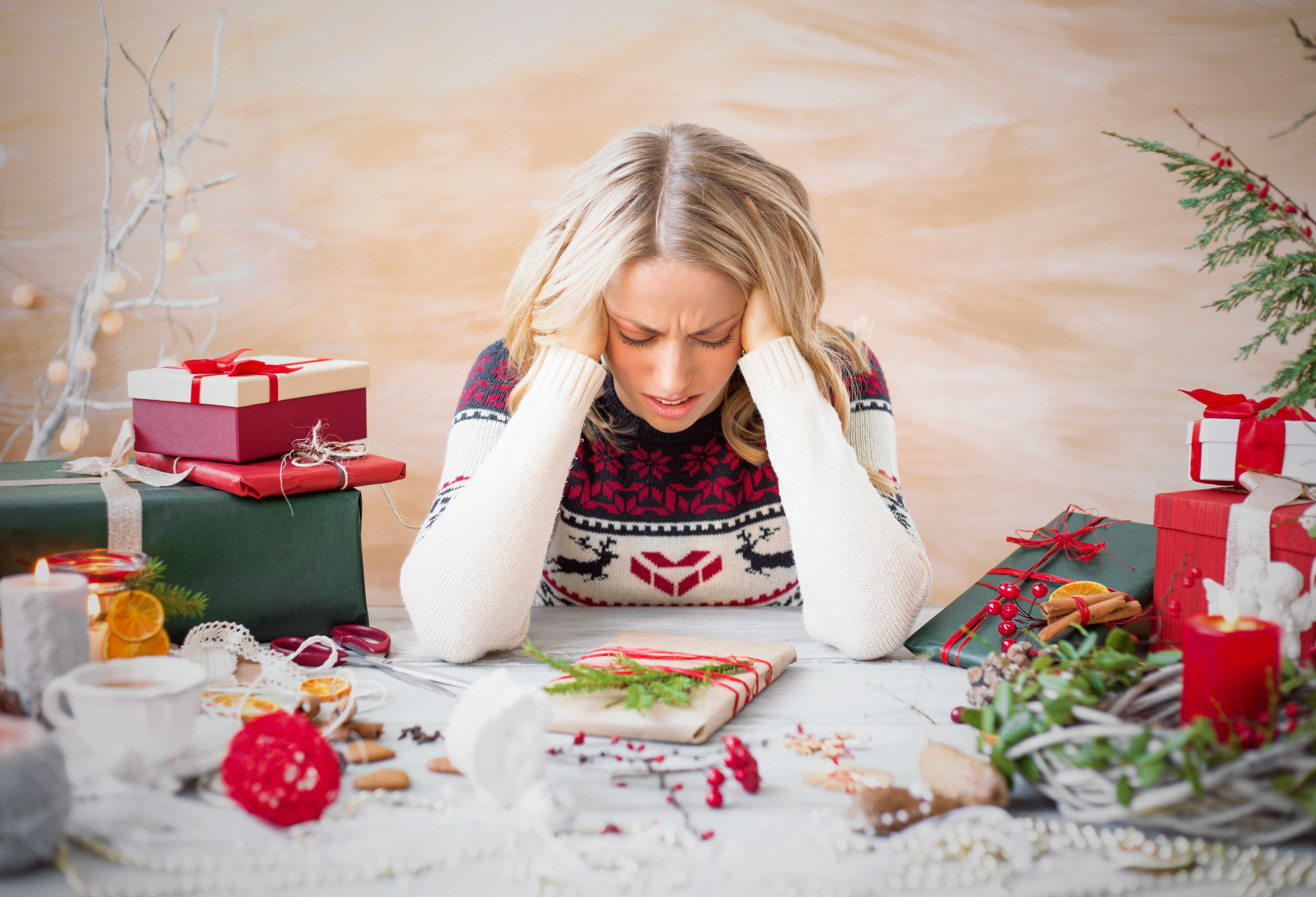 a woman tired and stressed, holding her head in her hands with presents and wrapping paper everywhere