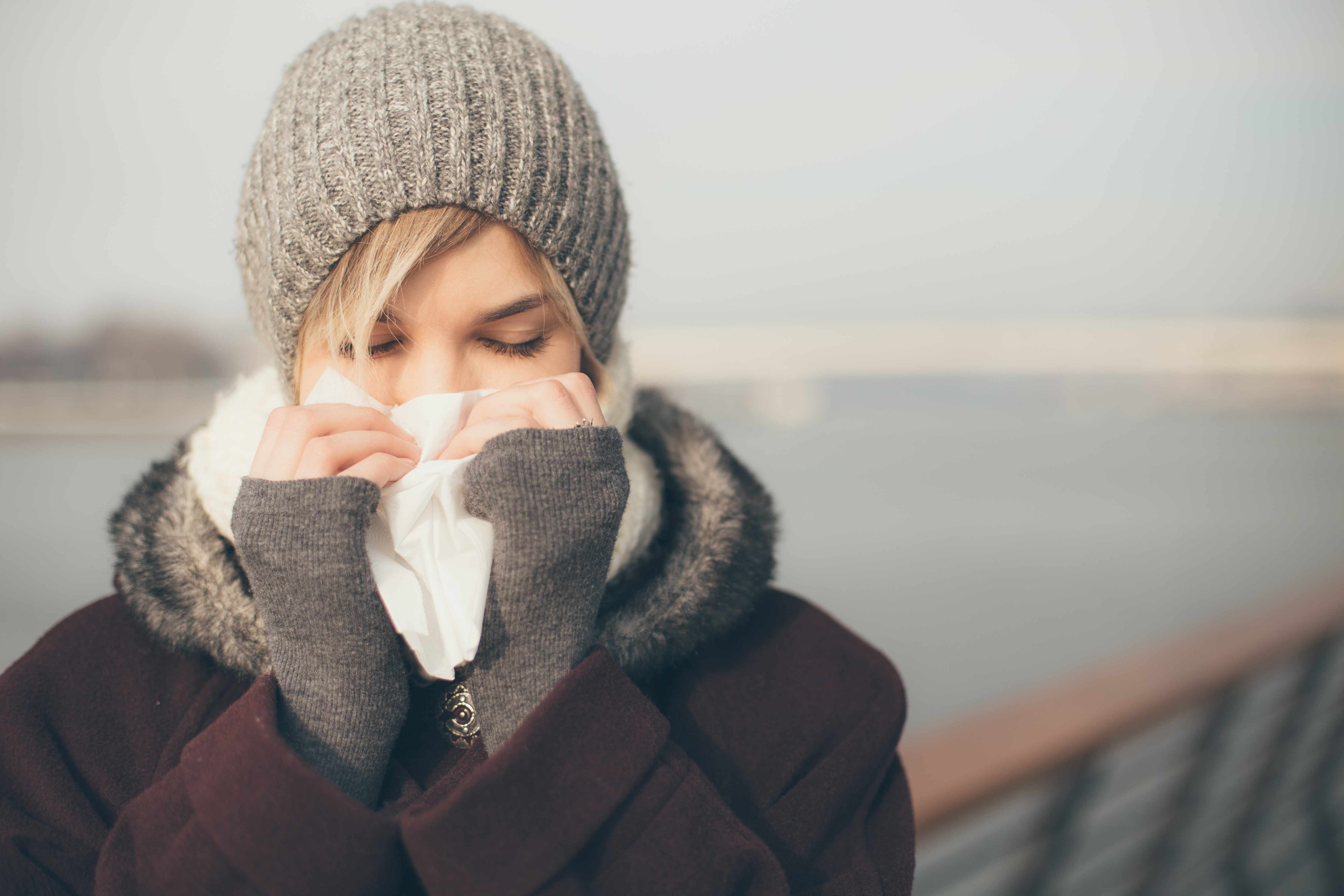 a woman bundled up in coat and hat in the cold outdoors blowing her nose
