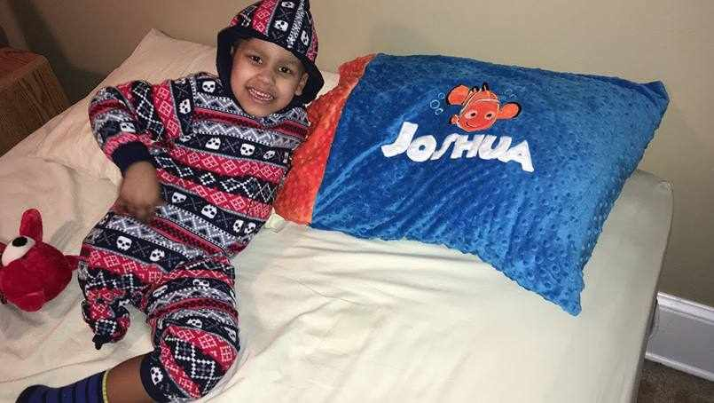 young patient Joshua smiling and resting on his bed