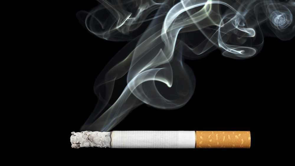 Un cigarrillo encendido, cuyo humo se enreda con el aire
