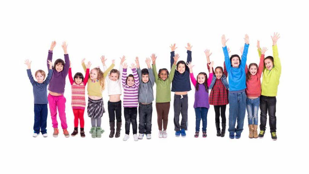 Un grupo de niños hacen fila mientras sonríen y levantan los brazos