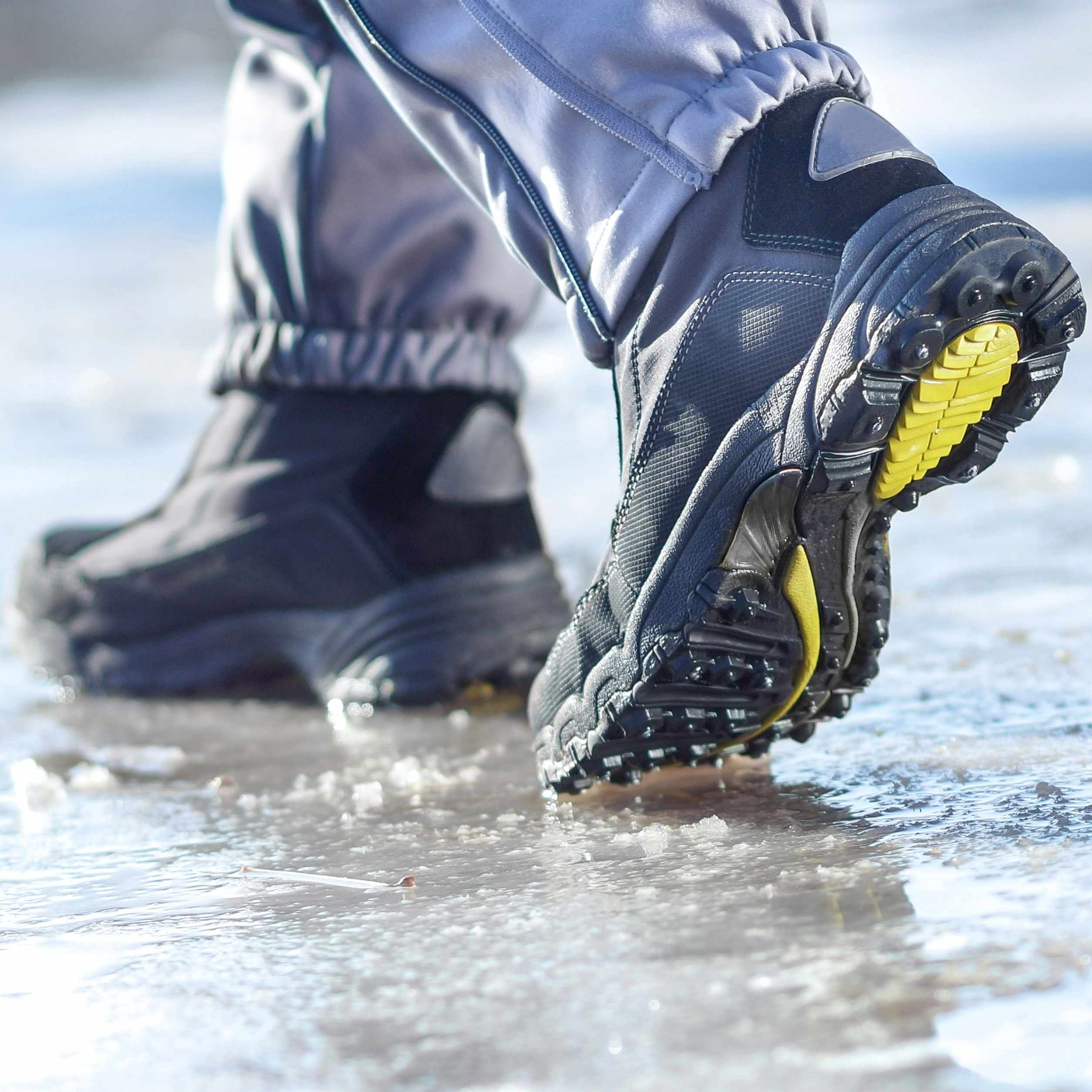 a person wearing winter boots and walking on slippery ice