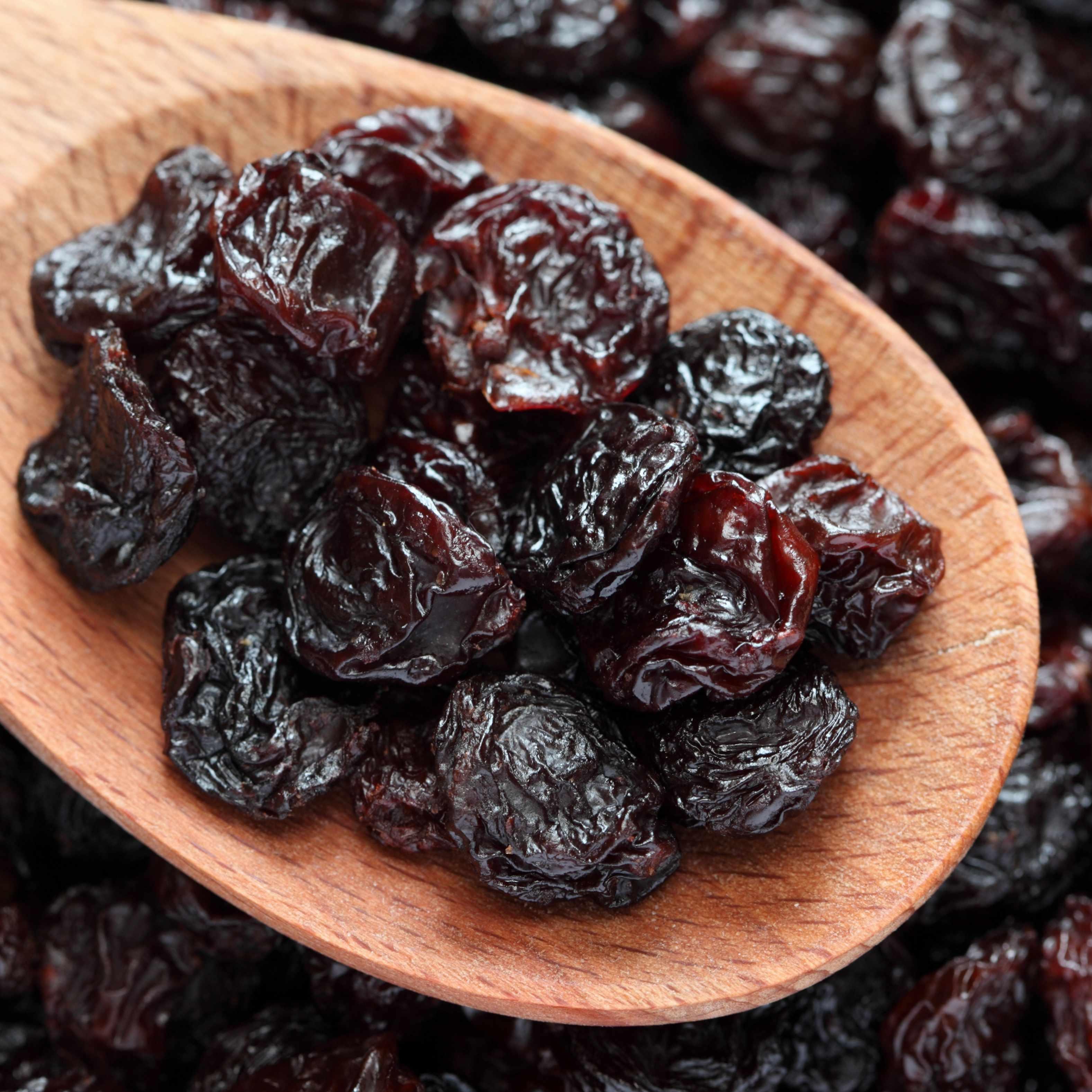 a wooden spoon full of healthy raisins