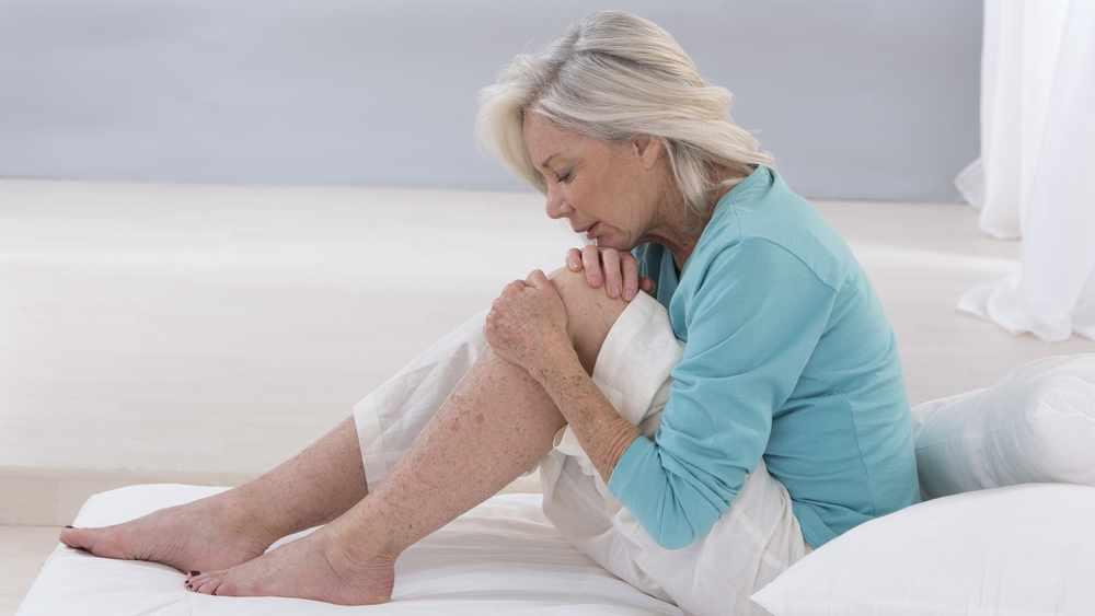 una anciana sentada en la cama hace muecas de dolor mientras se sostiene la rodilla