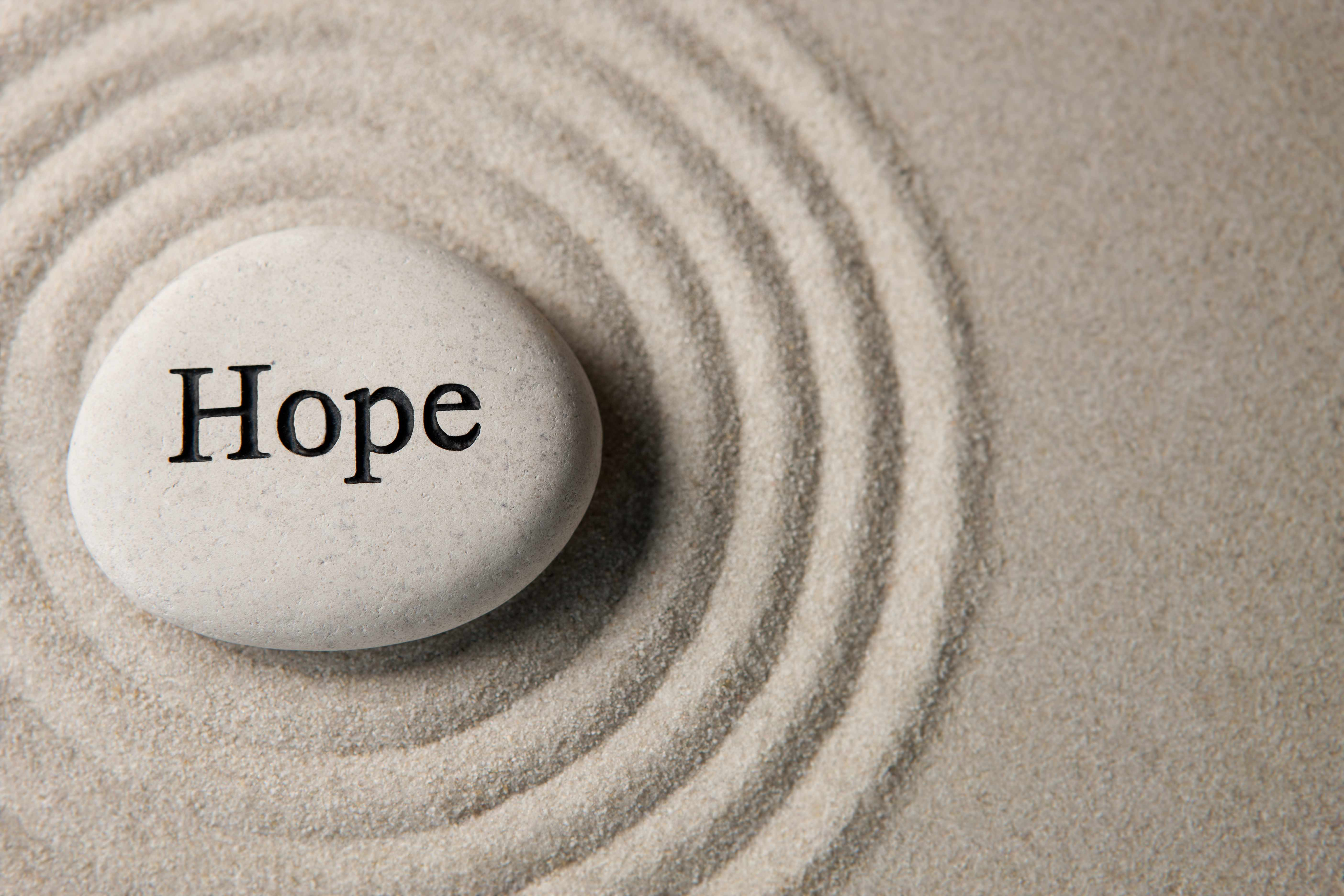 a stone in the sand with the word hope written on it