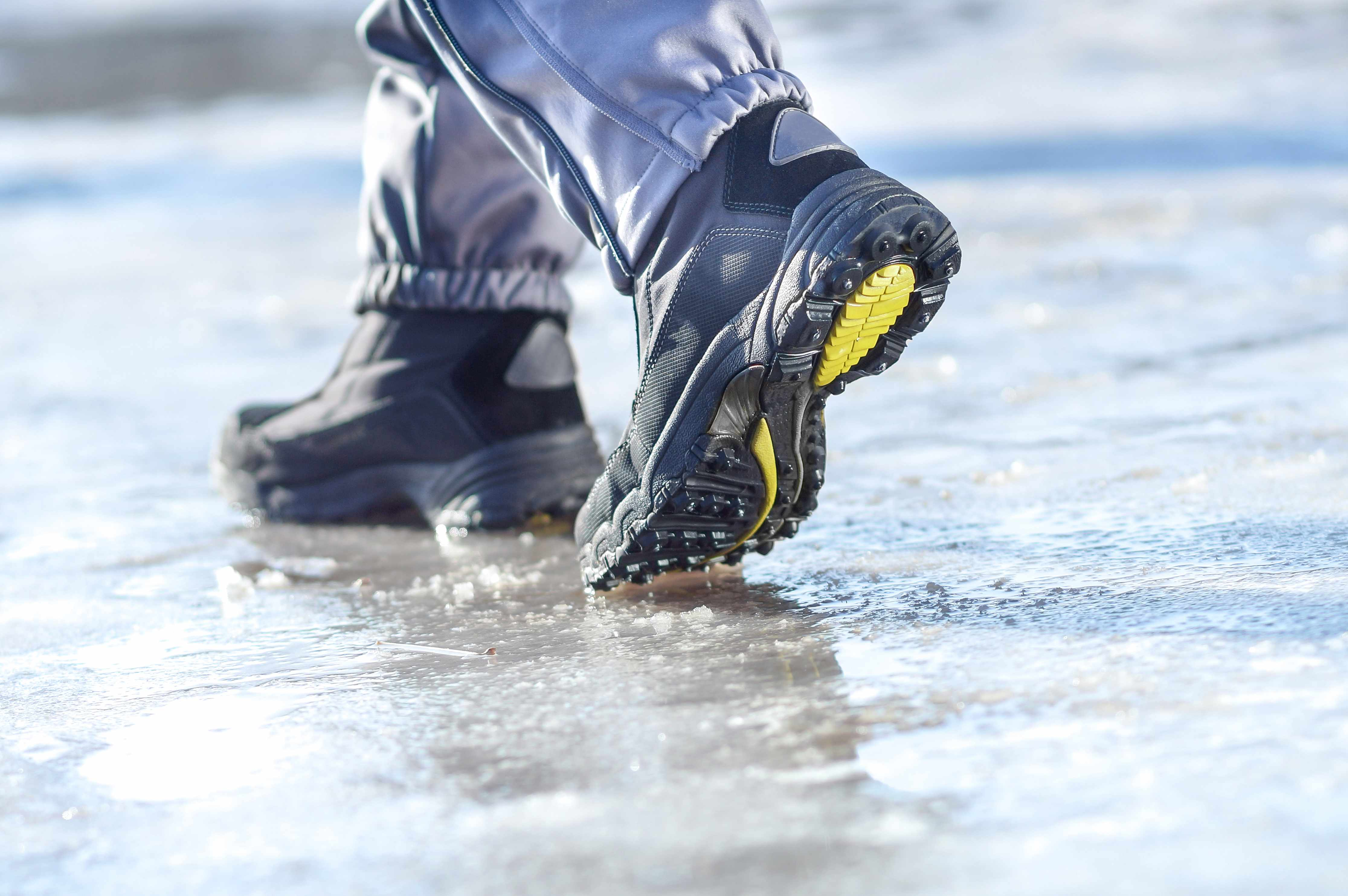 a person in winter boots walking a slippery ice