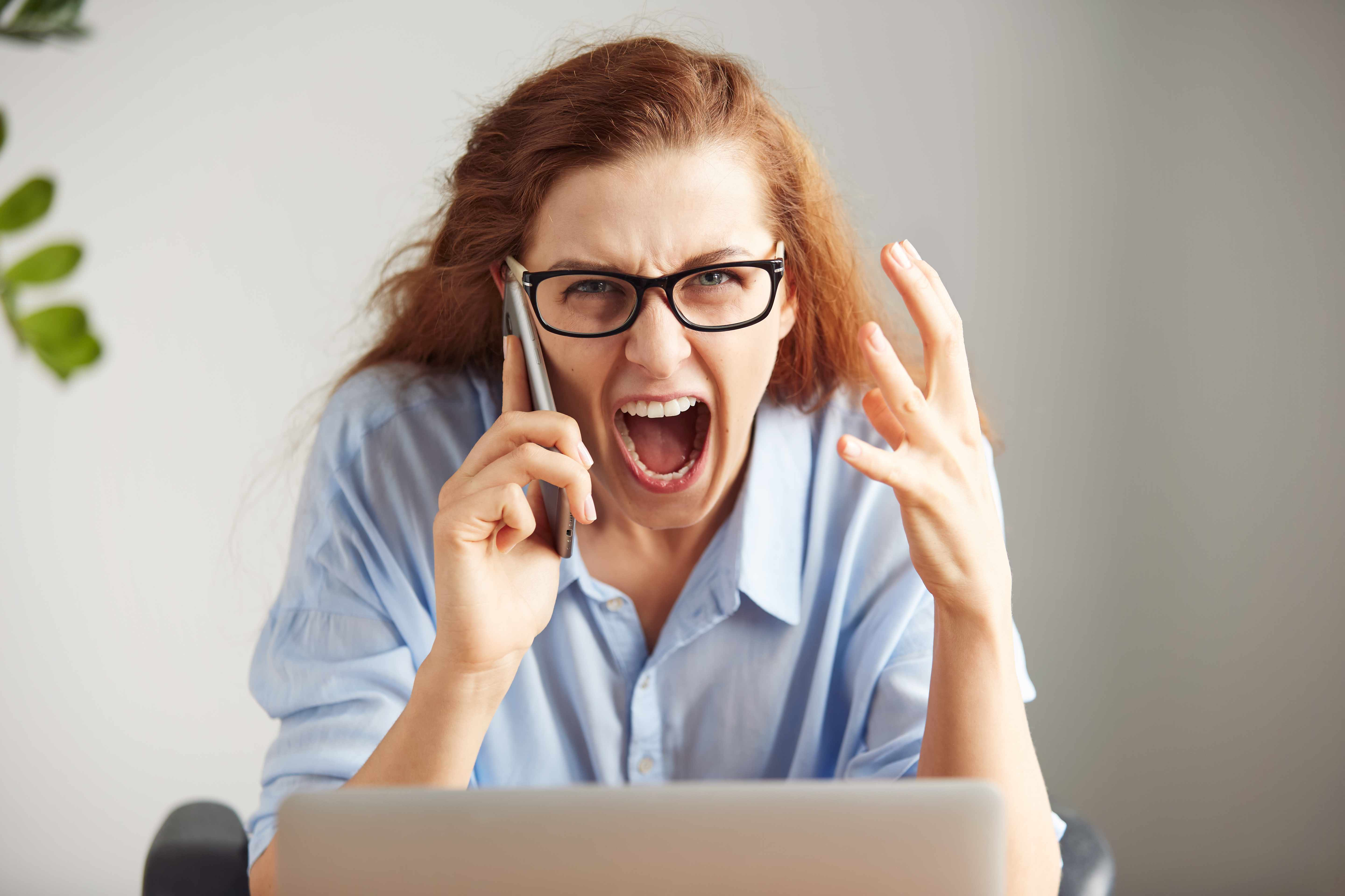 a woman wearing glasses, sitting at a desk angry and yelling into a phone