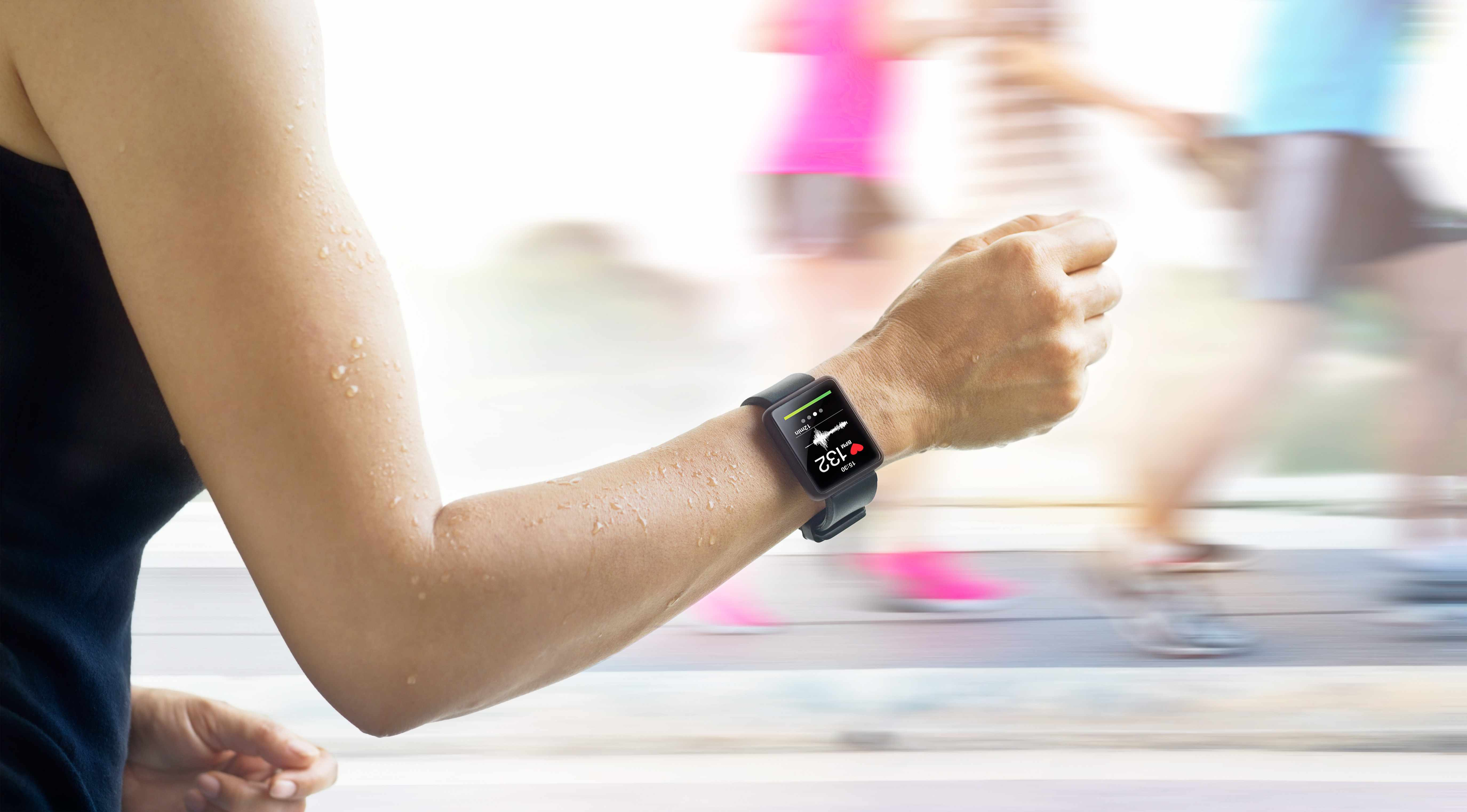 a woman running with an exercise monitor on her arm