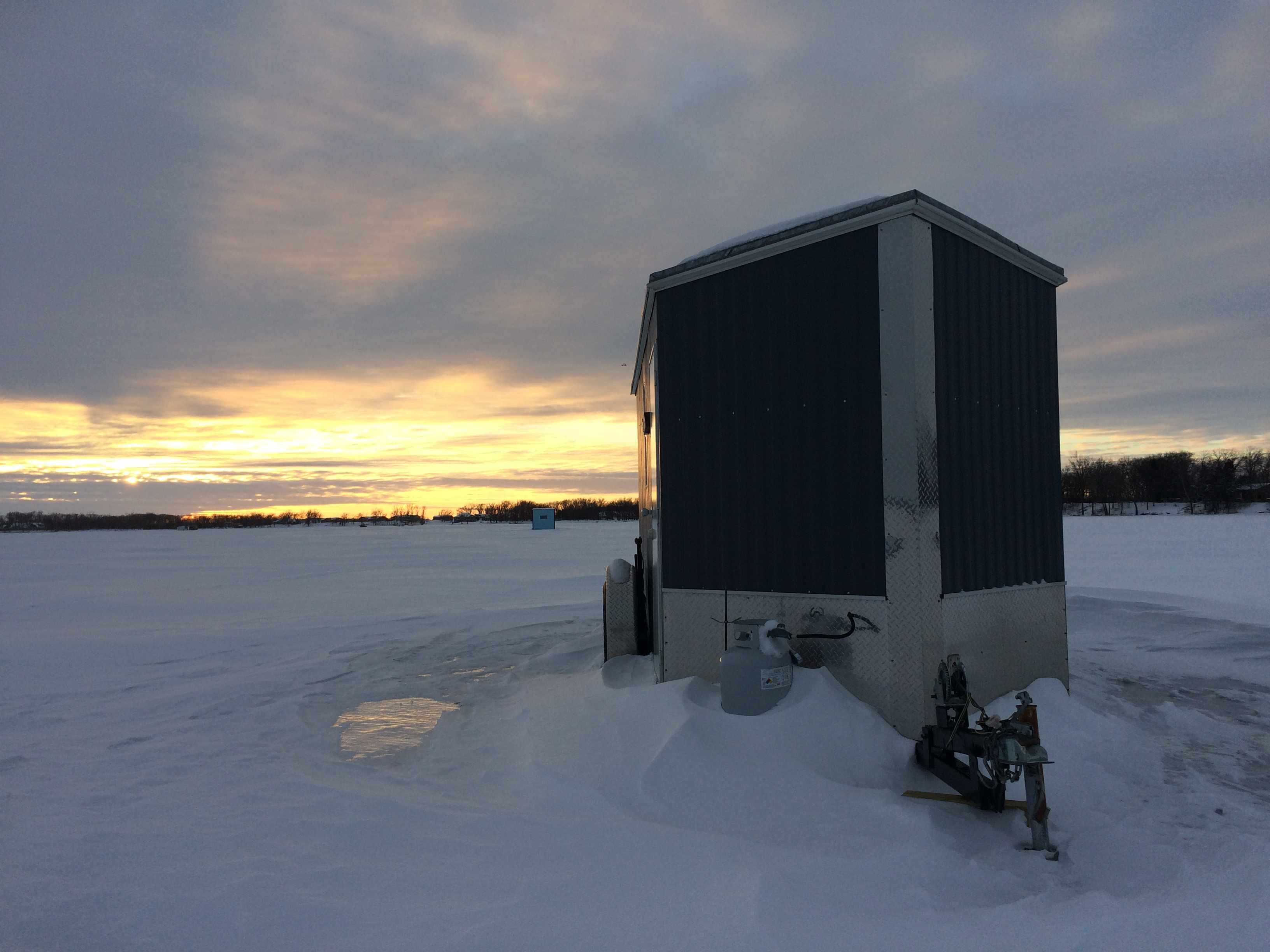 sunset on a frozen lake with ice fishing house in foreground